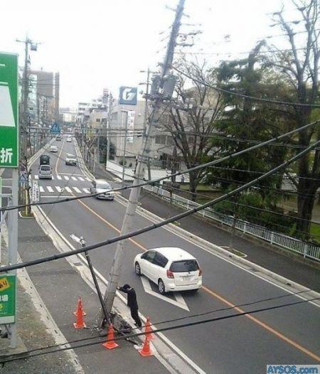 Man Holds up street pole