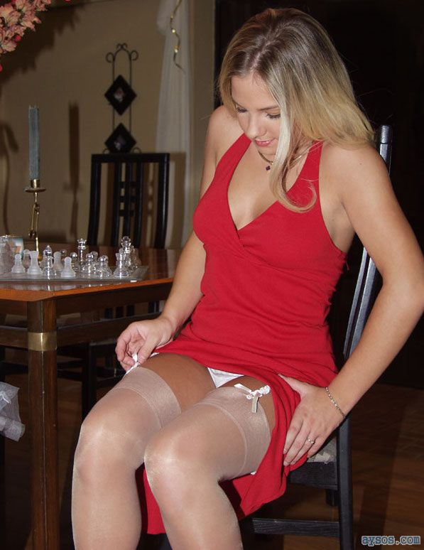 Hot wife wearing a sexy dress and white stockings pulls up her dress to show off her legs